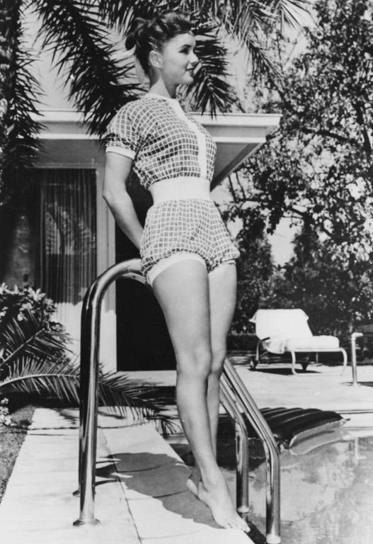 . Portrait of actress Debbie Reynolds wearing a shorts-suit and standing next to a swimming pool, circa 1955. (Photo by Keystone/Hulton Archive/Getty Images)