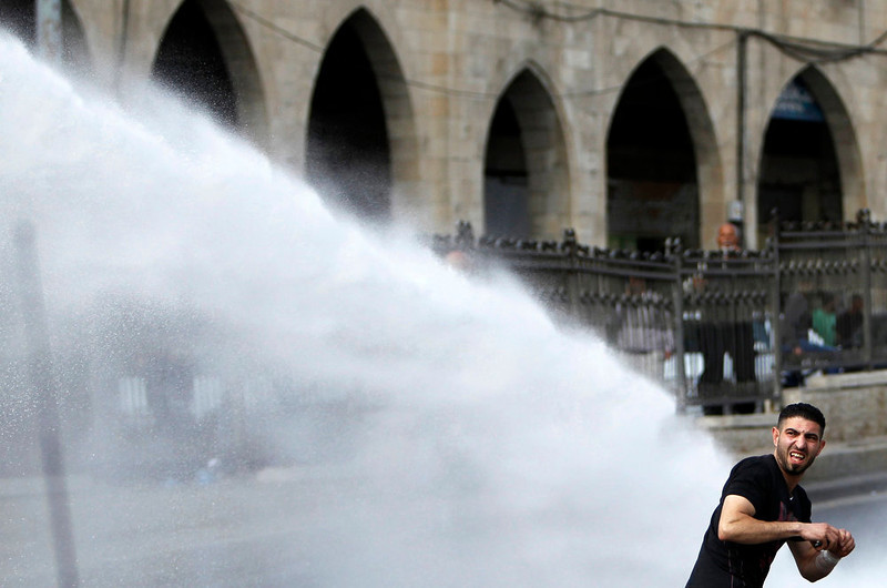 . A Palestinian protestor throws stones as he gets sprayed with water activated by Israeli security forces during clashes near Damascus Gate at Jerusalem\'s old city May 15, 2013. Palestinians clashed with Israeli forces in the occupied West Bank and at East Jerusalem on Wednesday during demonstrations to mark 65 years since what they call the Nakba (Catastrophe) when Israel\'s creation caused many to lose their homes and become refugees. REUTERS/ Ammar Awad