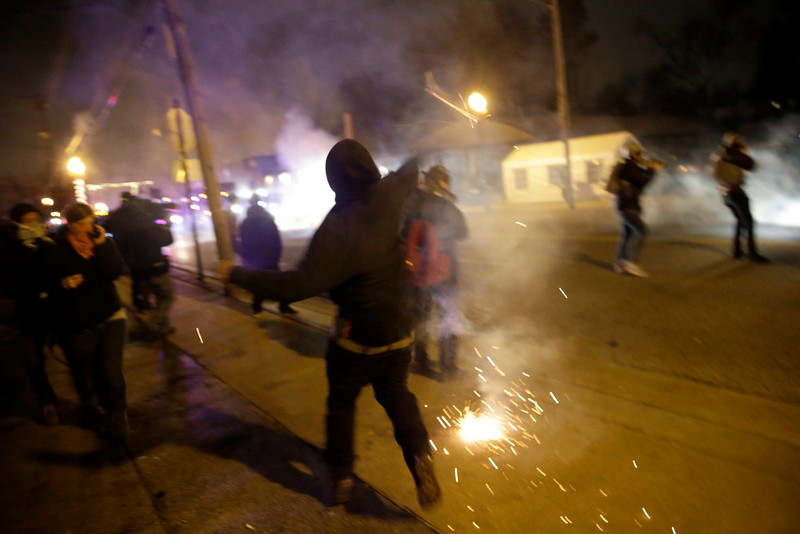 . Smoke fills the streets after the announcement of the grand jury decision not to indict police officer Darren Wilson in the fatal shooting of Michael Brown, an unarmed black 18-year-old, Monday, Nov. 24, 2014, in Ferguson, Mo. (AP Photo/David Goldman)
