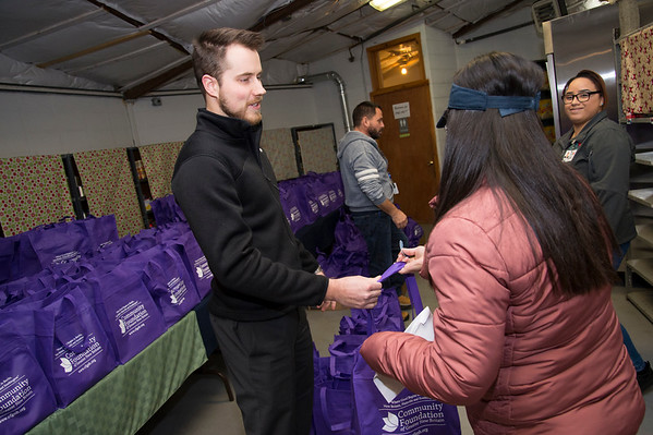 11/25/19 Wesley Bunnell | Staff Thanksgiving meals were distributed by HRA workers and volunteers on Monday evening at their Osgood Park location. Viktor Black, a volunteer part of a group from Hexcel Corporation, hands out bags of food to clients.