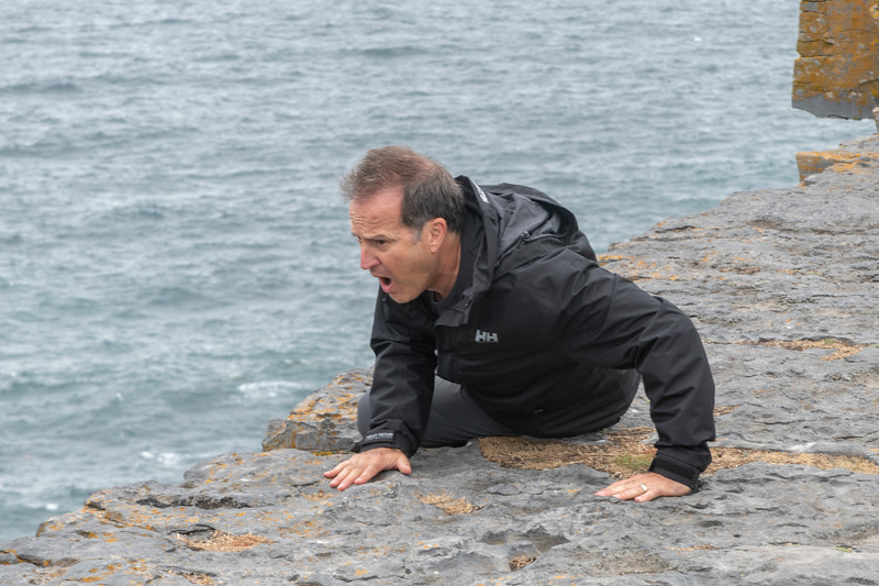 Man showing expression looking over the edge of cliff, Dun Aengus, Inishmore, Inishmore, Ireland