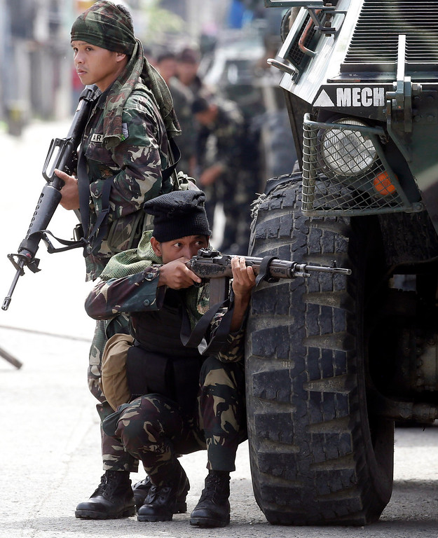 . A Government trooper aims his rifle in a continuing operation to rescue scores of hostages being used as human shields by Muslim rebels on the fourth straight day Thursday, Sept. 12, 2013 at Zamboanga city in southern Philippines. (AP Photo/Bullit Marquez)