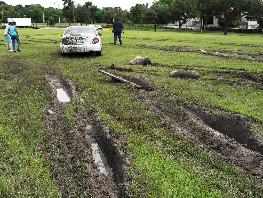 . Deep muddy ruts lead to a car stuck in a field Wednesday, May 27, 2015, in Houston. Several attempts at removal just added to the mess. The death toll from a barrage of storms and floods in Texas and Oklahoma climbed to at least 19 on Wednesday, with over a dozen people missing, and another round of rain threatened to complicate the cleanup in hard-hit Houston.  (AP Photo/Pat Sullivan)