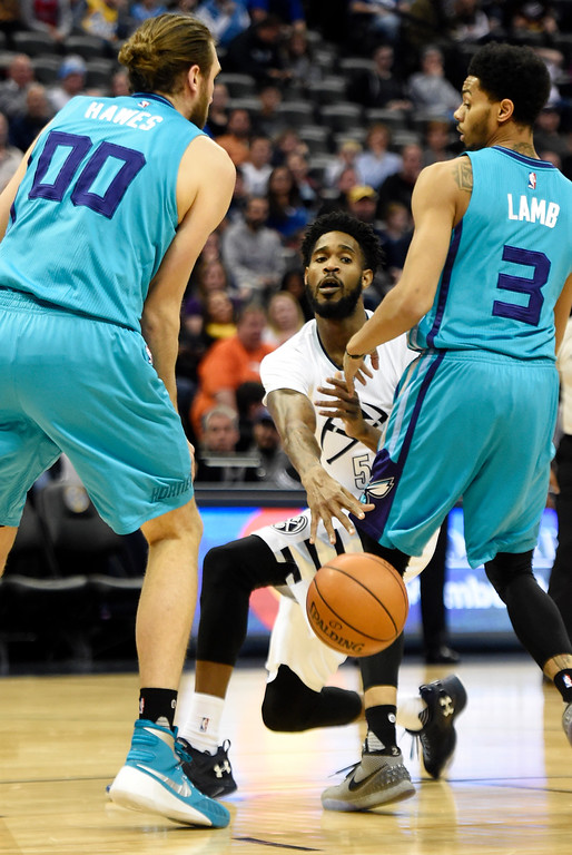 . Will Barton (5) of the Denver Nuggets passes between Spencer Hawes (00) of the Charlotte Hornets and Jeremy Lamb (3) during the first quarter. The Denver Nuggets hosted the Charlotte Hornets at the Pepsi Center on Sunday, January 10, 2016. (Photo by AAron Ontiveroz/The Denver Post)