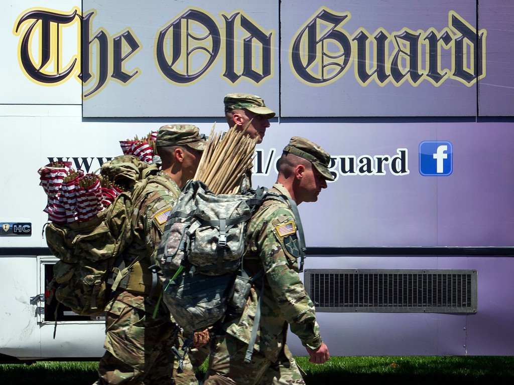 . Members of the Army 3d U.S. Infantry Regiment, The Old Guard, prepare to place flags on graves, in honor the nation\'s fallen military heroes during its annual Flags In ceremony at Arlington National Cemetery,  Thursday, May 24, 2018, in Arlington, Va. (AP Photo/Cliff Owen)