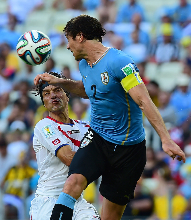 . Costa Rica\'s midfielder Cristian Bolanos and Uruguay\'s defender Diego Lugano vie for the ball during a Group D football match between Uruguay and Costa Rica at the Castelao Stadium in Fortaleza during the 2014 FIFA World Cup on June 14, 2014.   AFP PHOTO / RONALDO SCHEMIDT
