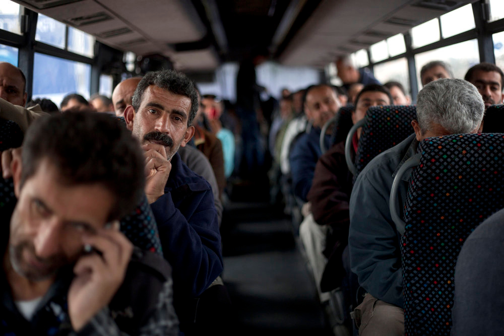 """. Palestinians laborers ride a Palestinian-only bus on route to the West Bank from working in Tel Aviv area, Israel, Monday, March 4, 2013. Israel\'s decision to launch a pair of \""""Palestinian-only\"""" bus lines in the West Bank condemned by critics as racism and hailed by Israel as a goodwill gesture have shined a light on the messy situation created by 45 years of military occupation and Jewish settlements. (AP Photo/Ariel Schalit)"""