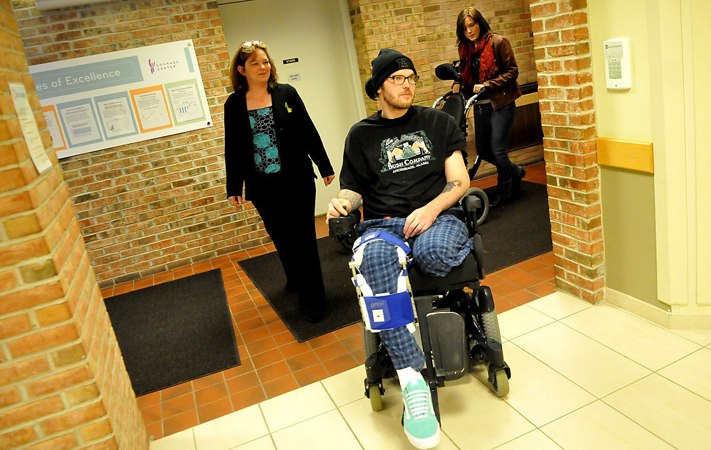. Zack Mohs negotiates the hallways of Courage Center, followed by his mother, Cheryl Young, and sister. Molly Miller. Mohs lost his left leg below the knee, among other injuries, in the hit-and-run. (Pioneer Press: John Doman)