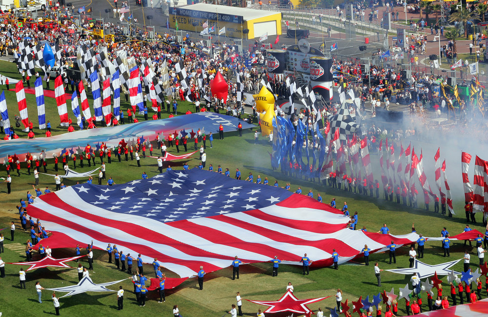 Description of . A large United States flag is unfurled during pre-race ceremonies prior to the start of the Daytona 500 at the Daytona International Speedway in Daytona Beach, Fla., on Sunday, Feb. 20, 2005. (AP Photo/David Graham)