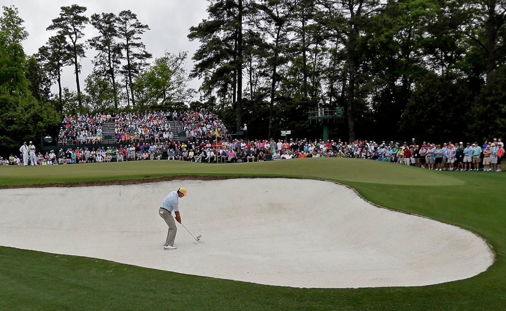Description of . Matt Kuchar hits out of a bunker on the first hole during the fourth round of the Masters golf tournament Sunday, April 14, 2013, in Augusta, Ga. (AP Photo/Charlie Riedel)