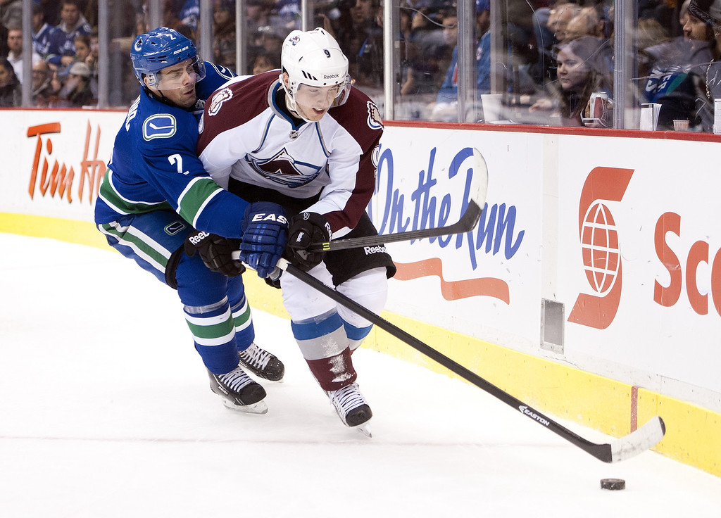 . Dan Hamhuis #2 of the Vancouver Canucks tries to poke the puck away from Matt Duchene #9 of the Colorado Avalanche during the first period in NHL action on December 08, 2013 at Rogers Arena in Vancouver, British Columbia, Canada.  (Photo by Rich Lam/Getty Images)