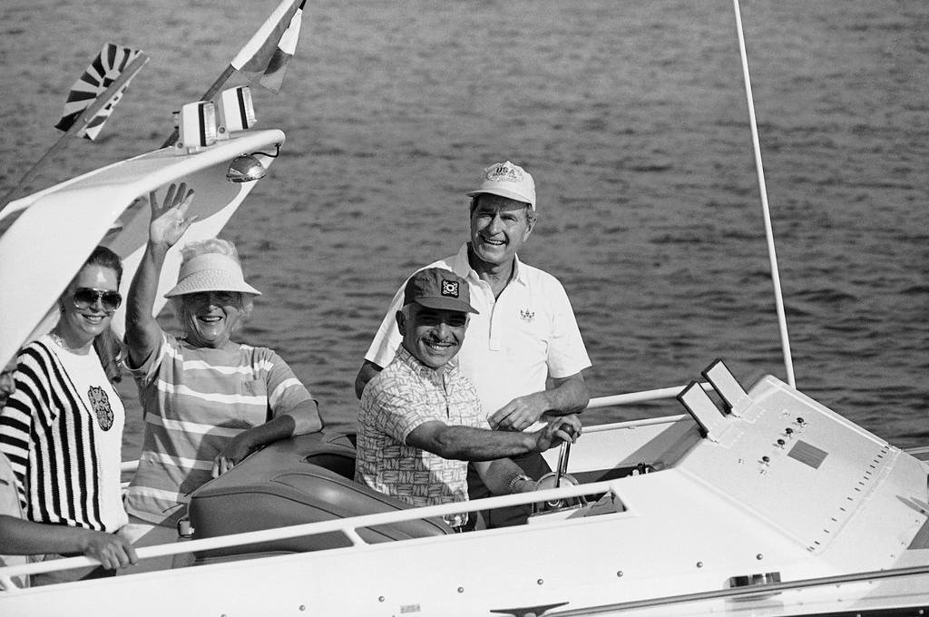 . With King Hussein of Jordan, at the helm, Vice President George H. W. Bush, standing, center, and their wives, Barbara Bush, second from left, and Queen Noor, cruise while staying at the king\'s summer guest house, Aug. 1, 1986, Aqaba, Jordan. (AP Photo/ Ron Edmonds)