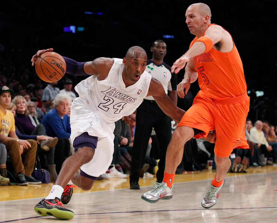 . Los Angeles Lakers\' Kobe Bryant (L) drives around New York Knicks\' Jason Kidd (R) during the second half of their NBA basketball game in Los Angeles December 25, 2012. REUTERS/Danny Moloshok