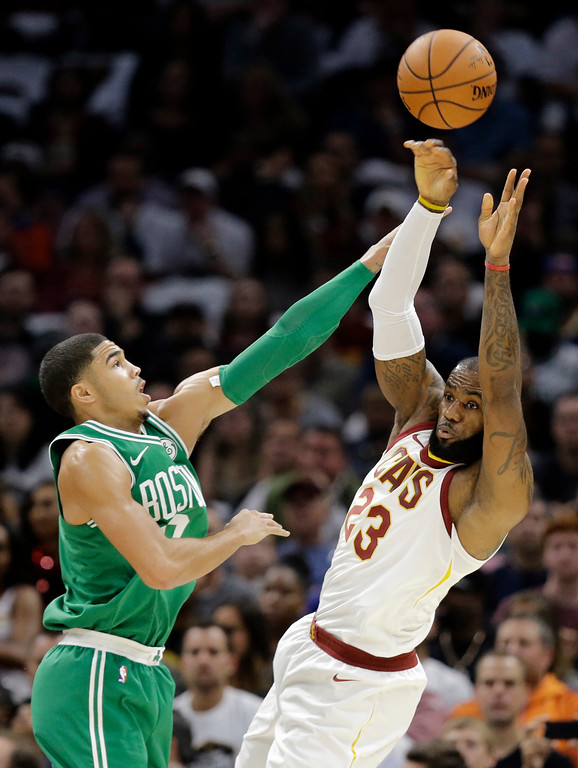 . Cleveland Cavaliers\' LeBron James, right, passes over Boston Celtics\' Jayson Tatum in the first half of an NBA basketball game, Tuesday, Oct. 17, 2017, in Cleveland. (AP Photo/Tony Dejak)