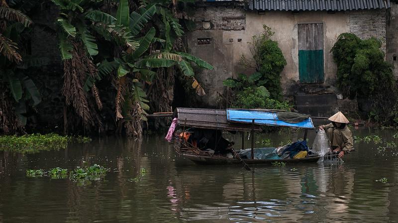 woman fishing in a river.  Vietnam, 2008.