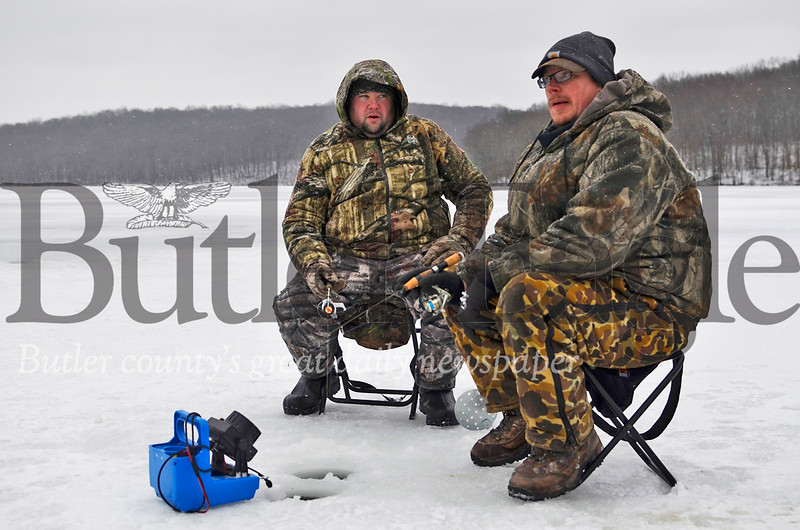 From left, Ryan Hills, 38, and Bill McKeown, 38, sit on the icy surface of Lake Arthur looking for fish on Thursday, Jan. 24, 2019. Tanner Cole/Butler Eagle