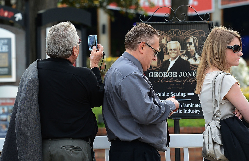 . A fan takes a photographs of a George Jones poster while waiting to enter the Grand Ole Opry House for the funeral of country music star George Jones on Thursday, May 2, 2013, in Nashville, Tenn. (AP Photo/Mark Zaleski)