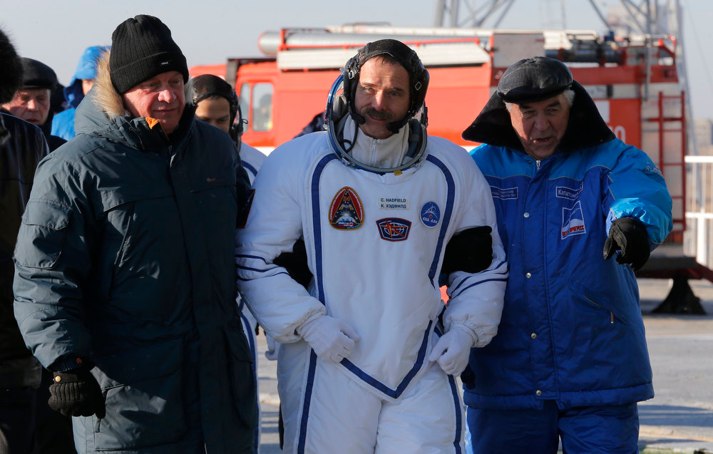 Description of . Canadian astronaut Chris Hadfield, crew member of the mission to the International Space Station, ISS, walks to the rocket prior the launch of Soyuz-FG  rocket at the Russian leased Baikonur cosmodrome, Kazakhstan, Wednesday, Dec. 19, 2012.  (AP Photo/Dmitry Lovetsky, pool)