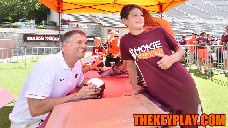 A young Hokie fan poses for a photo with head coach Justin Fuente. (Michael Shroyer/ TheKeyPlay.com)