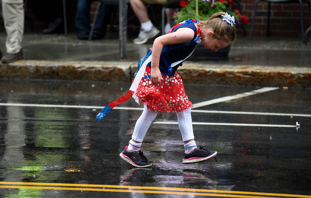 . Kayla Rice/Reformer A girl checks out her shoes while walking in the Brattleboro Fourth of July parade on Friday.