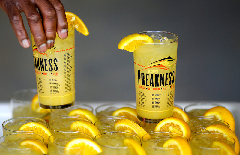 . Vendor Chudi Ugboaja sells Black-Eyed Susans at Pimlico Race Course in Baltimore, Saturday, May 17, 2014, before the 139th running of the Preakness Stakes horse race. (AP Photo/Patrick Semansky)