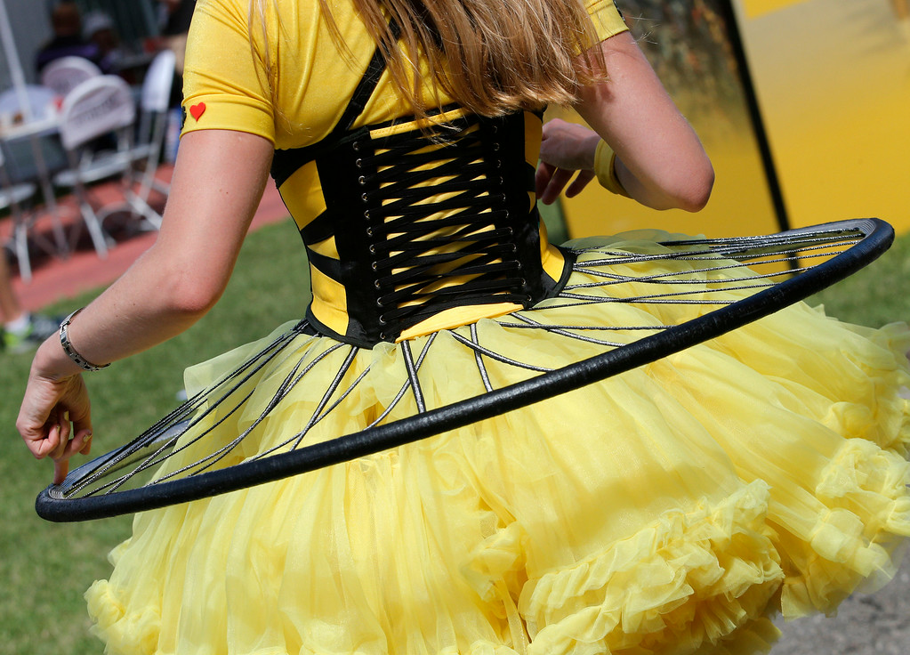 . An entertainer wears a dress in the colors of the overall leader\'s yellow jersey adorned with a bicycle wheel prior to the start of the tenth stage of the Tour de France cycling race over 161.5 kilometers (100.4 miles) with start in Mulhouse and finish in La Planche des Belles Filles, France, Monday, July 14, 2014. (AP Photo/Christophe Ena)