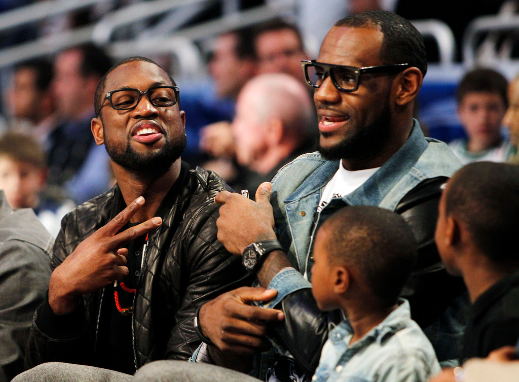 . Miami Heat\'s Dwyane Wade, left, and Lebron James sit courtside with James\' sons, LeBron Jr. and Bryce, during the NBA All-Star basketball festivities in Orlando, Fla., Saturday, Feb. 25, 2012. (AP Photo/Lynne Sladky)