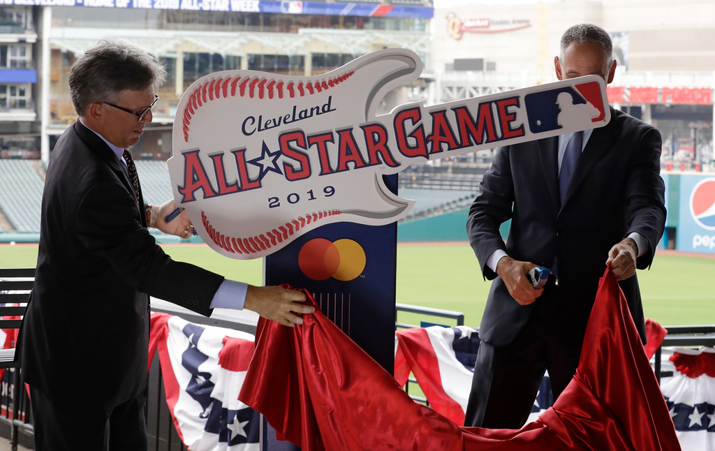 . Cleveland Indians owner Paul Dolan, left and Tony Petitti, MLB Deputy Commissioner, Business & Media, unveil the 2019 All-Star logo, Tuesday, Aug. 7, 2018, in Cleveland. Indians took the rock \'n\' roll route with a logo for the 2019 All-Star Game that won\'t offend anyone. The Indians are hosting the event for the sixth time, and next year\'s game coincides with the 25th anniversary of Progressive Field. (AP Photo/Tony Dejak)