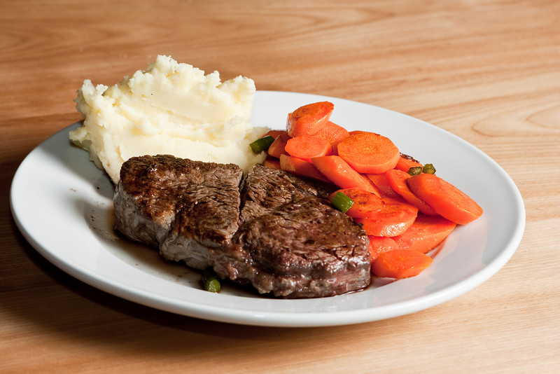 Beef tenderloin with garlic mashed potatoes and carrots with garlic scapes. Lighting: Alienbees B800 full power into shoot-through umbrella, camera right, 1/128 power 580EX II on camera for fill.