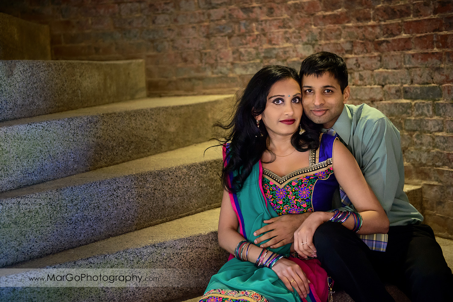 portrait of Indian couple sitting on the stairs of San Francisco Fort Point during engagement session