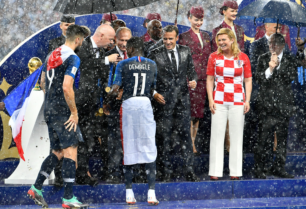 . FIFA President Gianni Infantino, Russian President Vladimir Putin, French President Emmanuel Macron and Croatian President Kolinda Grabar-Kitarovic, from left, wait in the pouring rain as France\'s Ousmane Dembele enters the podium after France won 4-2 in the final match between France and Croatia at the 2018 soccer World Cup in the Luzhniki Stadium in Moscow, Russia, Sunday, July 15, 2018. (AP Photo/Martin Meissner)