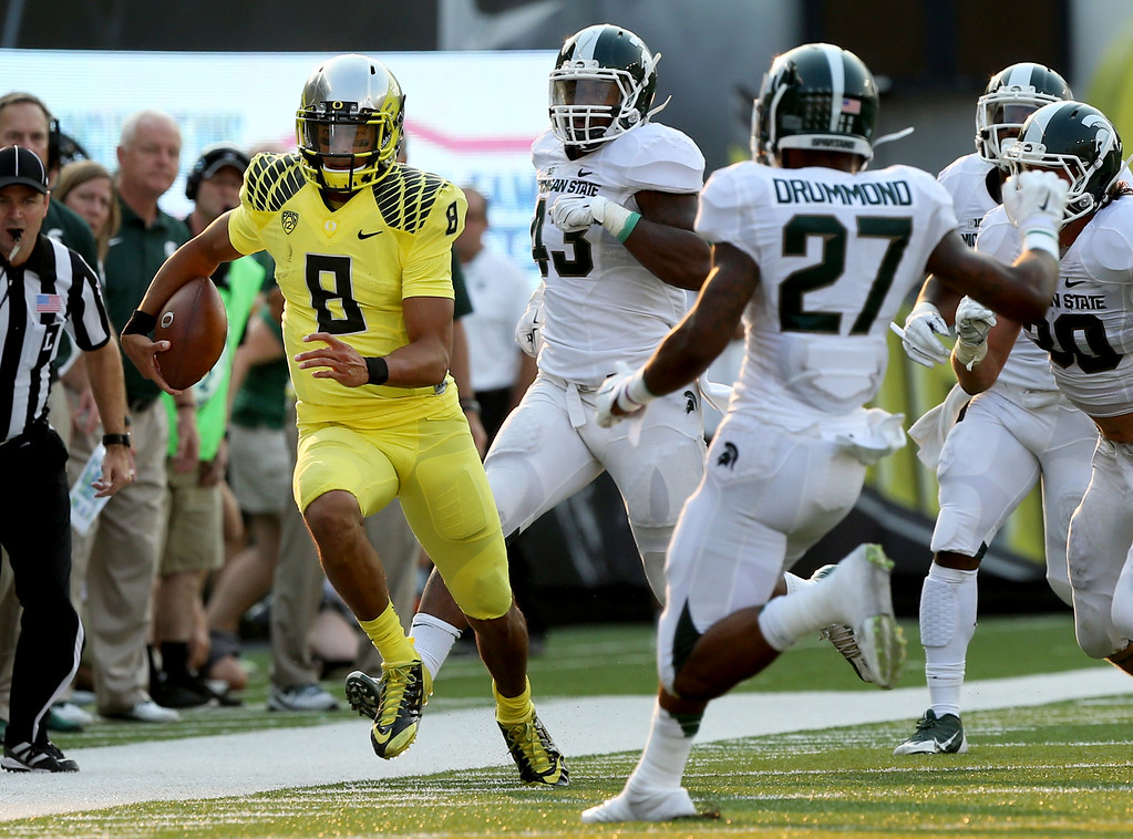 . Oregon quarterback Marcus Mariota, left, runs down the sidelines ahead of a host of Michigan State defenders during the 3rd quarter of their NCAA college football game in Eugene, Oregon, Saturday Sept. 6, 2014. (AP Photo/Chris Pietsch)