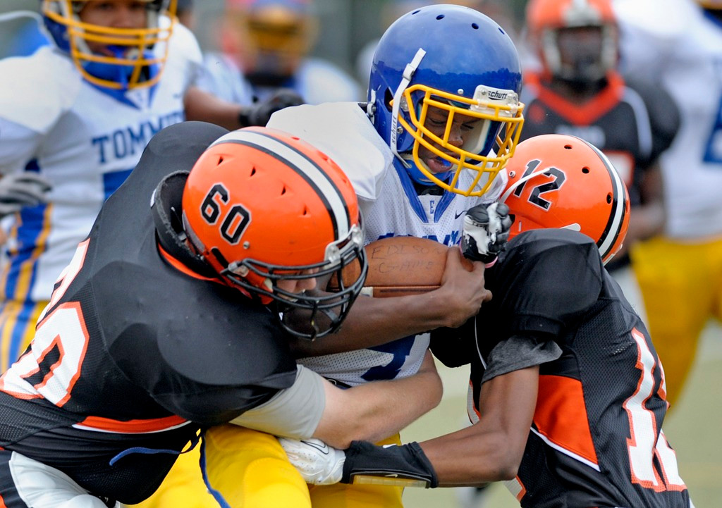 . Minneapolis Edison quarterback Talabi Montrea rushes for a short gain before being brought down by Humboldt\'s Jack Gilbertson, left, and Dionte Brown in the first half. (Special to the Pioneer Press: A.J. Olmscheid)