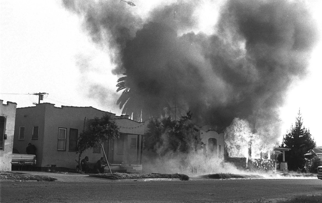 . Weapon-wielding police officers crouch nearby as flames destroy a suspected hideout for three Symbionese Liberation Army members in the south-central portion of Los Angeles, May 17,1974. (AP Photo)
