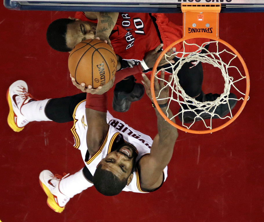 . Toronto Raptors\' DeMar DeRozan, top, drives to the basket against Cleveland Cavaliers\' Kyrie Irving during the fourth quarter of an NBA basketball game Saturday, Nov. 22, 2014, in Cleveland. The Raptors defeated the Cavaliers 110-93. (AP Photo/Tony Dejak)