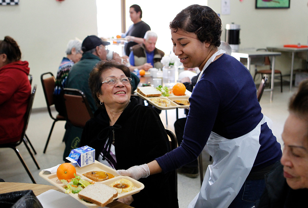 . At right, volunteer Monique Gaines, serves Teodora Nolasco, left, during a county subsidized lunch at the Eastside Neighborhood Center of the Catholic Charities of Santa Clara County in San Jose, Calif. on Wednesday, Feb. 27, 2013. (LiPo Ching/Staff)