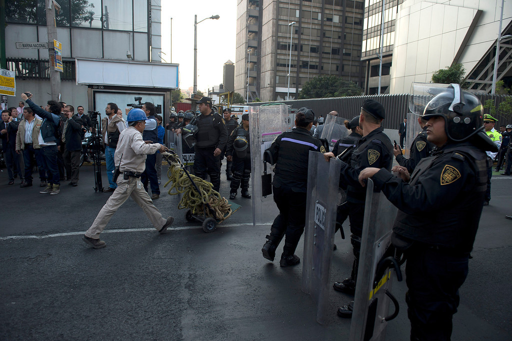 . Police stand guard as a rescue team heads for the skyscraper that houses the headquarters of state-owned Mexican oil giant Pemex in Mexico City on January 31, 2013, following a blast inside the building. An explosion rocked the skyscraper, killing at least 14, as a plume of black smoke billowed from the 54-floor tower, according to official sources.   YURI CORTEZ/AFP/Getty Images