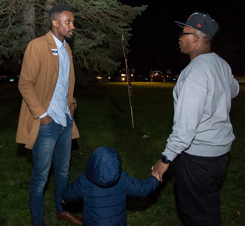 11/05/19 Wesley Bunnell | StaffrrDemocratic nominee for mayor Chris Porcher speaks to supporters Cortez Neal and son Zion, age 4, outside of Slade Middle School on Tuesday evening.