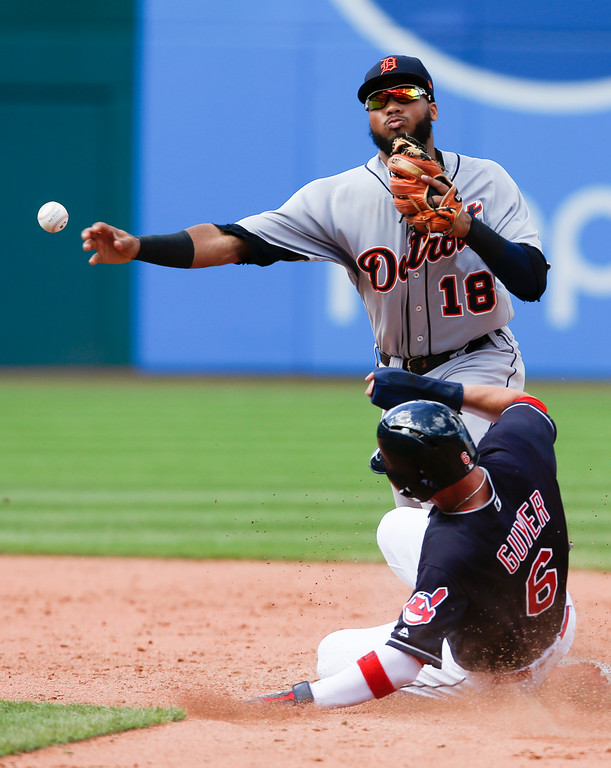 . Detroit Tigers\' Dawel Lugo forces out Cleveland Indians\' Brandon Guyer at second base and throws out Eric Haase at first base to complete the double play during the sixth inning of a baseball game, Sunday, Sept. 16, 2018, in Cleveland. (AP Photo/Ron Schwane)