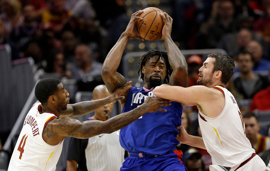 . Cleveland Cavaliers\' Iman Shumpert, left, and Kevin Love, right, put pressure on Los Angeles Clippers\' DeAndre Jordan, center, during the first half of an NBA basketball game, Friday, Nov. 17, 2017, in Cleveland. (AP Photo/Tony Dejak)