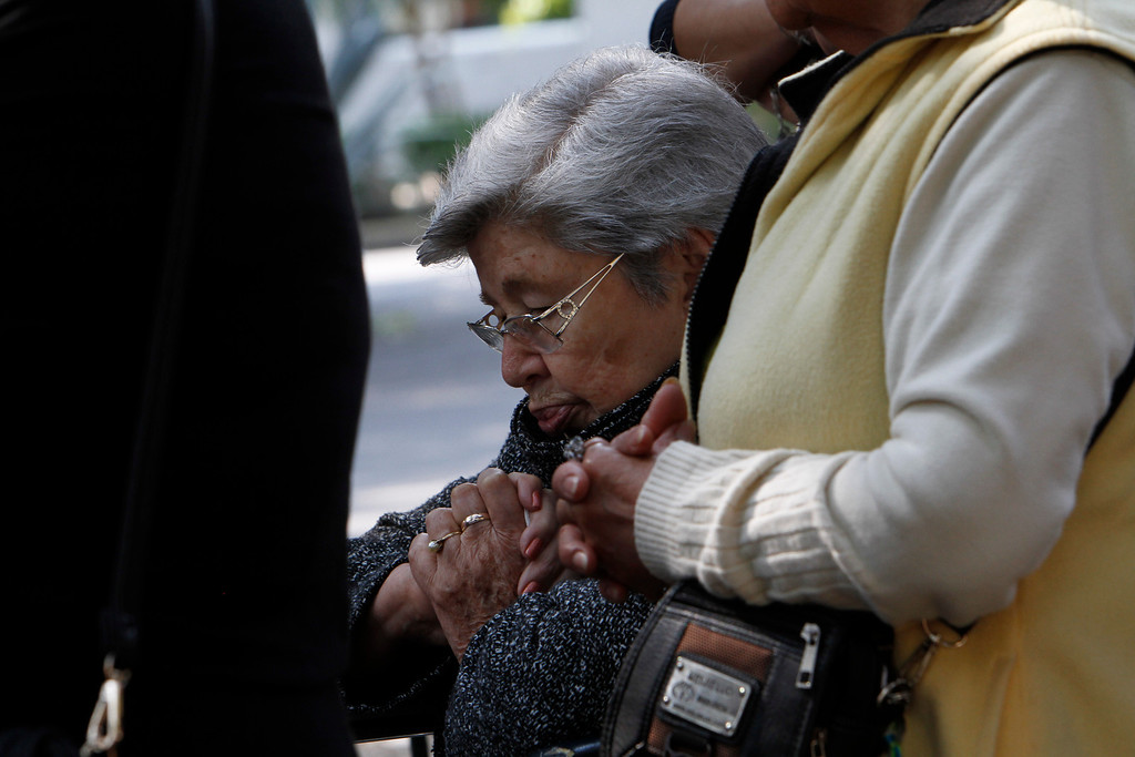 . People who were participating in a Holy Week procession stop and pray after a strong earthquake jolted Mexico City, Friday, April 18, 2014. A powerful magnitude-7.2 earthquake shook central and southern Mexico but there were no early reports of major damage or casualties. (AP Photo/Marco Ugarte)