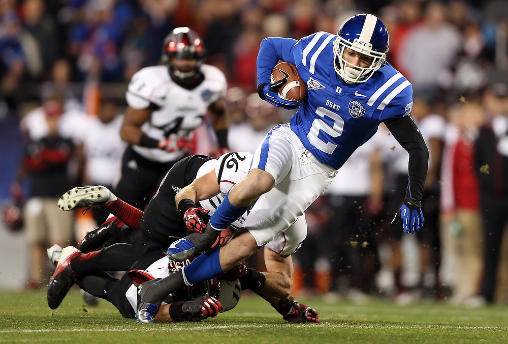 . Drew Frey #26 of the Cincinnati Bearcats dives to tackle Conner Vernon #2 of the Duke Blue Devils during their game at Bank of America Stadium on December 27, 2012 in Charlotte, North Carolina.  (Photo by Streeter Lecka/Getty Images)