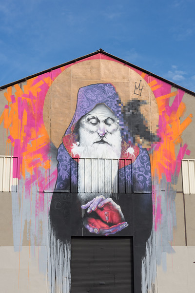 A purple and black wizard with a white beard painted on the side of a building in Arles, France.