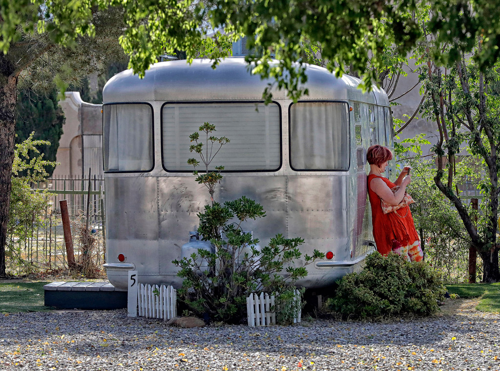 . A guest takes a photo with her smartphone while leaning on a Spartan Manor travel trailer, Wednesday, April 26, 2017, at the Shady Dell Trailer Court in Bisbee, Ariz. Vintage aluminum travel trailers with period furnishings are used as guest rooms. Retro trailers such as Airstream, Spartan Royal Mansion, Airfloat, Boles Aero and El Rey are used in the trailer court located 10 miles from the Mexican border. (AP Photo/Matt York)