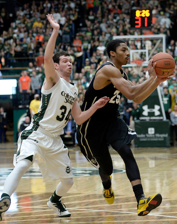 . CU\'s Spencer dinwiddie looks for an open teammate while dribbling the ball past David Cohn during an NCAA game against CSU on Tuesday, Dec. 3, 2013, at the Moby Arena in Fort Collins. Jeremy Papasso/ Camera
