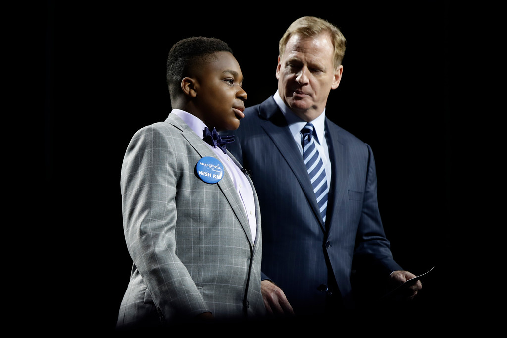 . T.J. Owuanibe, 14, left, walks with NFL commissioner Roger Goodell to announce the Baltimore Ravens\' selection during the first round of the 2017 NFL football draft, Thursday, April 27, 2017, in Philadelphia. (AP Photo/Matt Rourke)