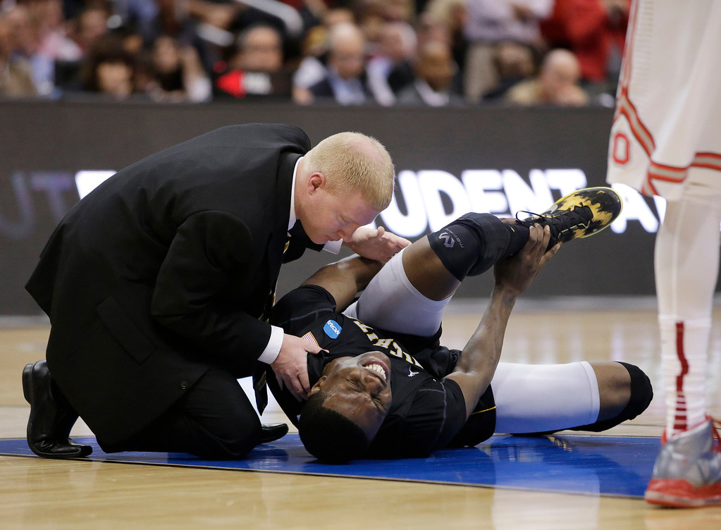 . Wichita State\'s Cleanthony Early, right, is examined after suffering an injury during the second half of the West Regional final against Ohio State in the NCAA men\'s college basketball tournament, Saturday, March 30, 2013, in Los Angeles. (AP Photo/Mark J. Terrill)