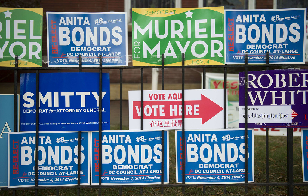 . Campaign signs are seen outside a polling place as voters cast their ballots for the midterm elections in Washington, DC, November 4, 2014. AFP PHOTO / Saul  LOEB/AFP/Getty Images