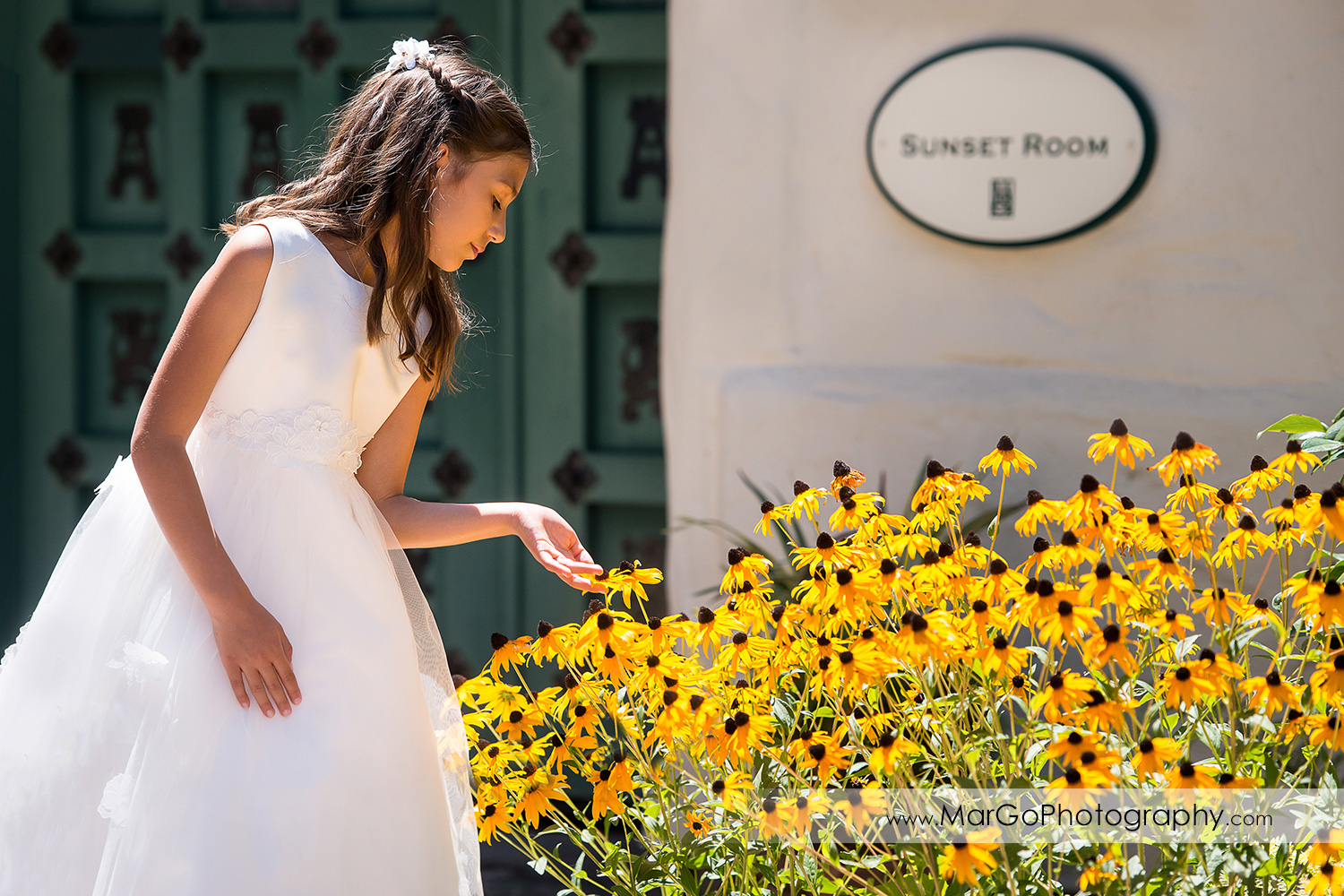 first communion girl in white dress watching yellow flowers at Cafe Wisteria in Menlo Park