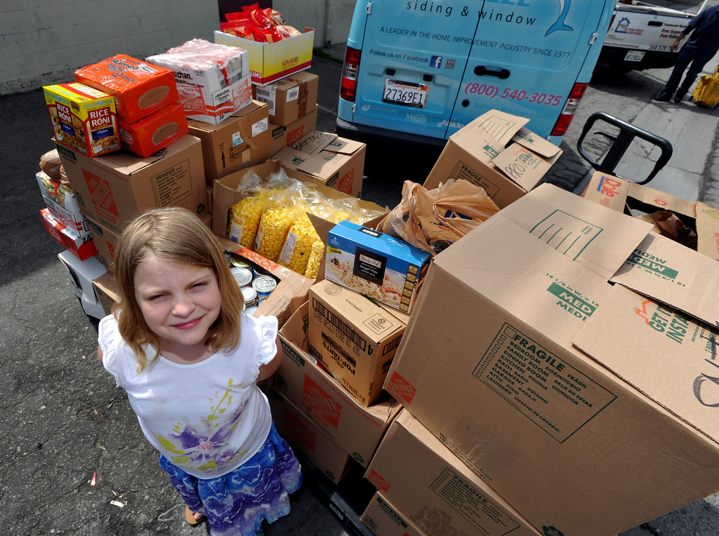 . Halli Brainard, 9, of Whittier, stands with the food that she collected and donated to the Interfaith Food Center in South Whittier on Monday March 25, 2013. Brainard has been collecting money and food over the last three weeks and donated an extimated 1,200-pound of foons.